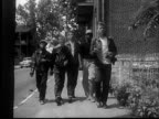 '1950s WS Five boys about walking up sidewalk carrying bricks moving past camera/ St. Louis, Missouri/ AUDIO'