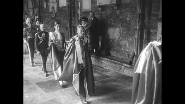 1950s footage of George VI wearing ceremonial attire and followed by a page holding the train of his robe / Note exact year not known