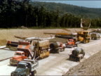 1950s high angle wide shot of trucks and construction vehicles at highway construction site / USA / audio
