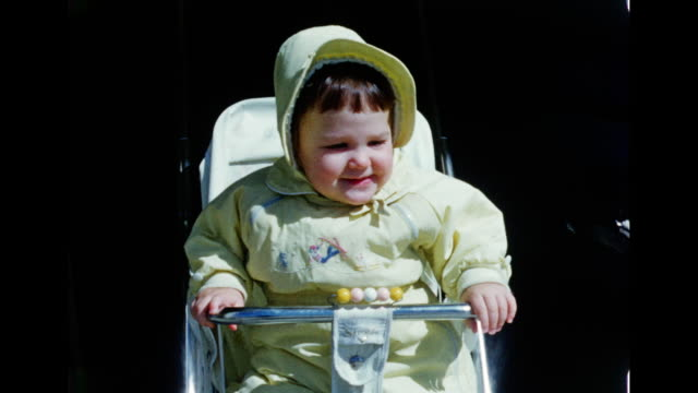 1950s Home Movie, Baby girl on her stroller smiling at camera