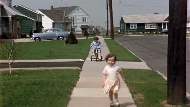 1950s long shot young girl running and young girl riding tricycle down neighborhood sidewalk toward CAM