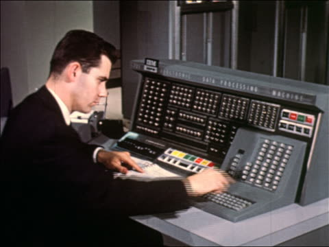1950s man in dark suit pushing buttons at console of IBM 705 computer