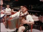 1950s man in traditional Austrian costume playing accordion on restaurant patio