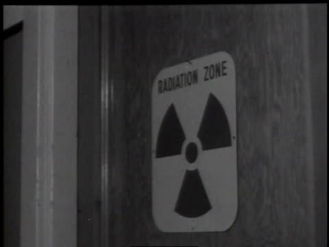 1950s CU man opening a door with a radiation warning sign on it / Hanford, Washington, United States