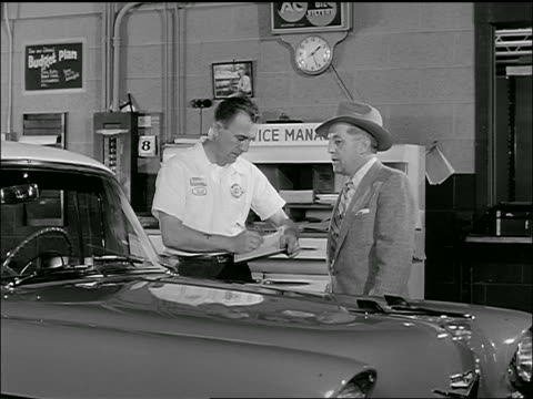 B/W 1950s man talking to mechanic who is writing next to car in garage