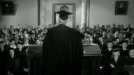 1950s medium shot senior man in cap and gown making speech at podium / audience in background