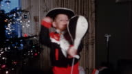 1950s medium shot young boy in cowboy costume punching bag in living room / part of Christmas tree in background