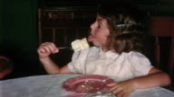 1950s medium shot young girl licking piece of cake on fork