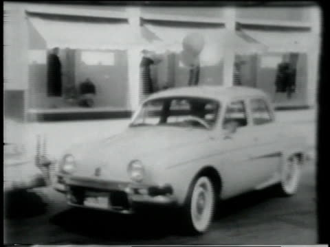 1950s MONTAGE Man with briefcase rollerskating past Renault Dauphine parked at curb, which then pulls out and drives through traffic and on highway