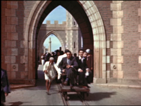 1950s people riding carts on rails pushed by running men through archway on city street / Cairo, Egypt