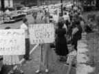 B/W 1950s prosegregation protestors with children standing with mispelled signs outside of school