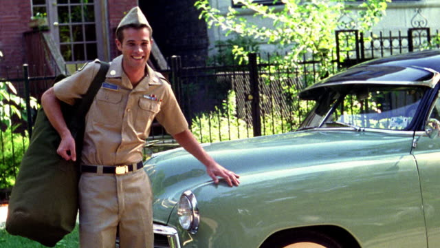 1950s REENACTMENT MS soldier in uniform carrying duffel bag + posing next to car