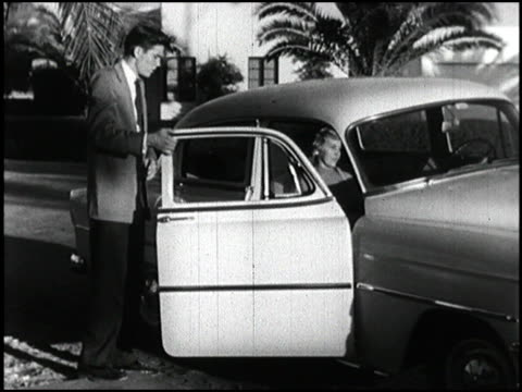 WS 1950s teenage boy in jacket and tie opens the door for his date She climbs into the car He walks around to the driver's side climbs in and they...