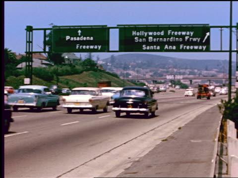 1950s traffic on freeway in Los Angeles / signs for Pasadena, Hollywood + San Bernardino Freeways