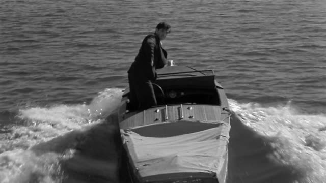 1950s wide shot Man in suit piloting motorboat firing gun