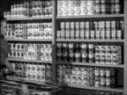 B/W 1950s woman taking can off supermarket shelf