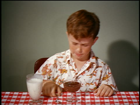 1950s/60s redheaded boy drinking mile + eating chocolate pudding in studio