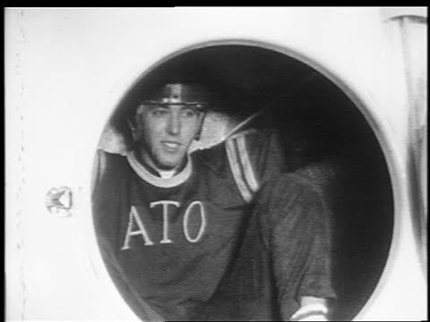 B/W 1950s/60s teen boy in fraternity sweater + helmet spinning in clothes dryer / newsreel