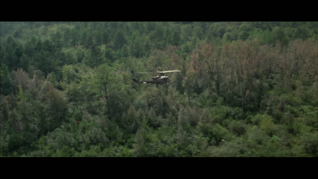 1960s AERIAL WS TS Military helicopter in flight low over jungle