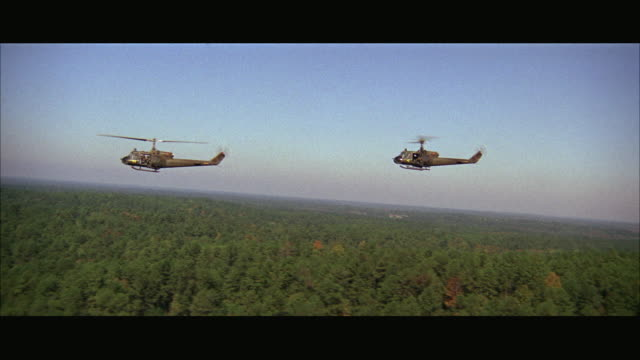 1960s WS AERIAL Military helicopters flying over jungle