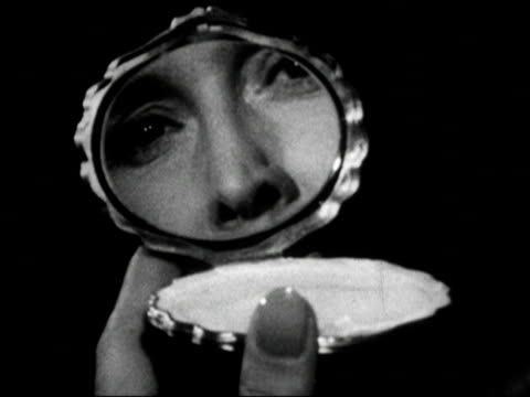 1960s Black and white Close up woman opening compact / woman's face reflected in mirror / woman breathing on mirror and fogging it up / AUDIO