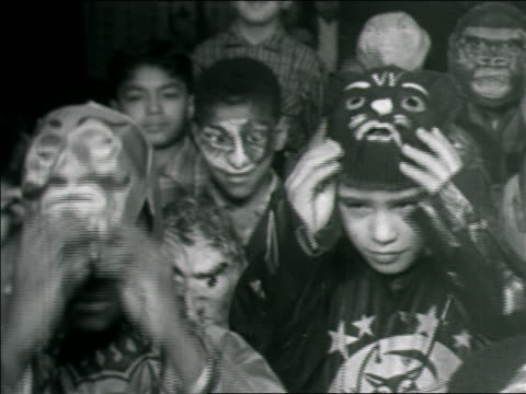 B/W 1960s Black + Hispanic boys in Halloween costumes putting masks over faces / others in background