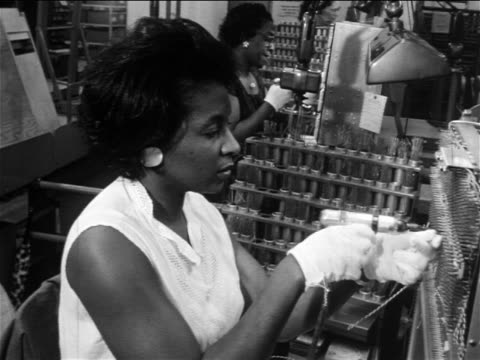 B/W 1960s Black woman using small drill in factory / documentary
