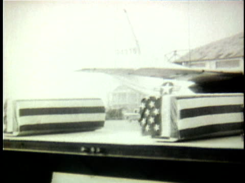 1960s B/W MONTAGE Flagdraped coffins of dead US soldiers being loaded onto military transport plane during early years of Vietnam War / South Vietnam