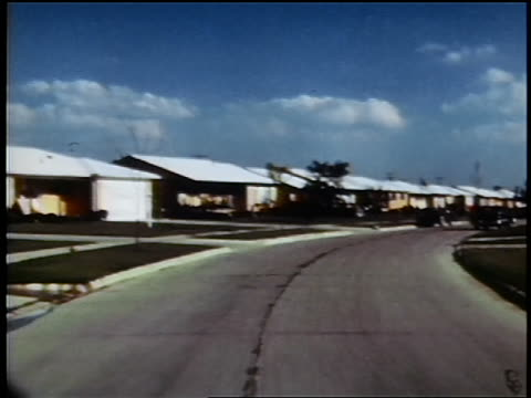1960s car point of view on suburban street with identical houses / Detroit suburb / industrial
