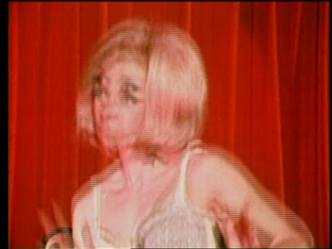 1960s close up blonde go-go girl dancing to music in front of red curtain