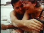 1960s close up couple lying on beach listening to radio / man turning knob / industrial