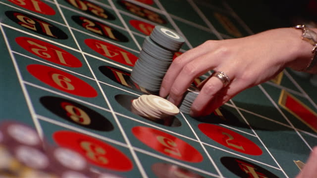 1960s close up hands placing chips on roulette table / croupier's hands pushing chips