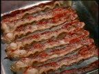 1960s close up strips of bacon cooking on griddle