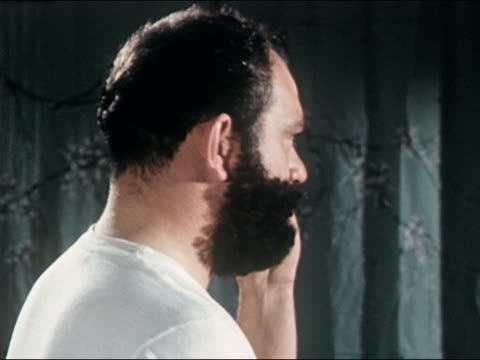 1960s close up view over shoulder of man shaving beard / turning to look at CAM with half of face shaved