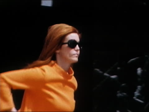 1960s close up zoom out woman wearing sunglasses walking tiger down city street / Los Angeles