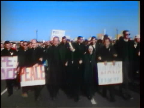 1960s crowd of priests nuns carrying posters marching in peace demonstration / Washington DC