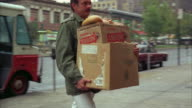 1960s MS PAN Delivery man carrying large box of bread into bakery