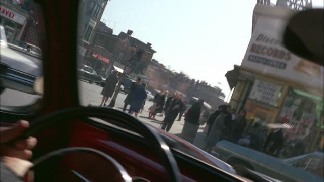1960s WS POV Driving along business street through heavy traffic