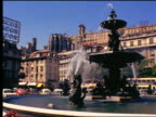 1960s fountain with traffic + buildings in background (Rossio Square) / Lisbon, Portugal