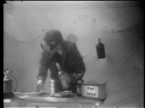 B/W 1960s GRAINY underwater MS man in suit + mask pouring drinks at underwater bar + answering telephone
