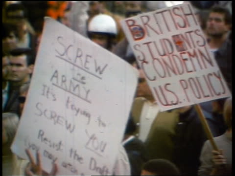 1960s high angle PAN crowd of protesters shouting holding signs giving peace sign at demonstration