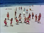1960s high angle long shot boys in swimsuits playing volleyball on beach / Los Angeles / educational