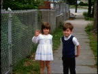 1960s HOME MOVIE two children standing on sidewalk waving at camera