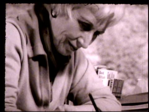 LILLIAN SMITH MS Lillian Smith sitting at outdoor desk writing w/ pen