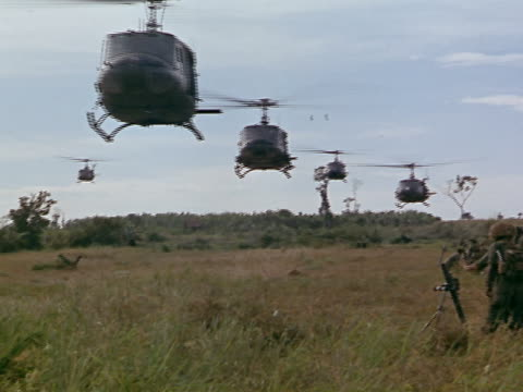 1960s long shot fleet of Bell UH1 Iroquois helicopters flying low over the ground / Vietnam