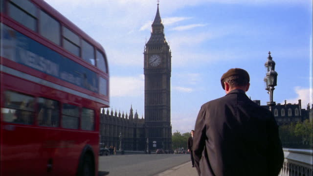 1960s low angle man closing umbrella and walking across bridge w/Big Ben in background / London