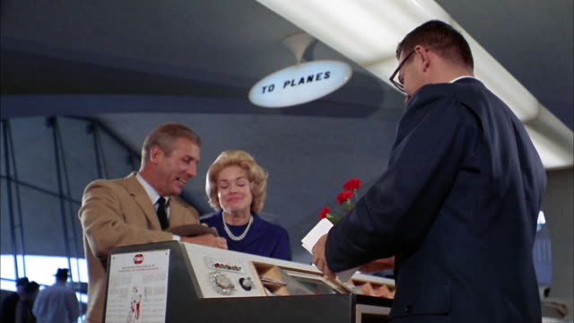 1960s low angle medium shot man and woman handing plane tickets to agent at counter / agent tagging piece of luggage
