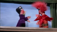 1960s low angle medium shot one puppet beating another with stick in puppet show / puppet applauding