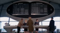 1960s low angle wide shot man and woman talking to female airline agents behind counter w/flight schedule in background