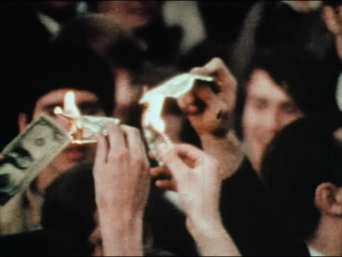 1960s medium shot antiwar demonstrators burning US dollar bills during Vietnam War / AUDIO